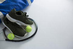 Sports shoe and tennis balls on racket by bag Stock Photo