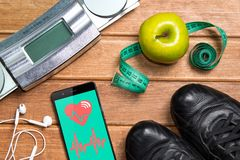 Sports shoes , Apple , scales, and a phone with health card on a. Wooden background. Mobile app health sensor for measuring health .WIFI  app measuring health Stock Photography