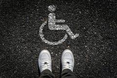 Sports Shoes on Asphalt. Disable People Sign on Asphalt Stock Image
