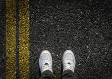 Sports Shoes on Asphalt. Double Yellow Sign on Asphalt Stock Photos