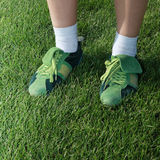 Sports shoes. Feet of woman dressed in green sports shoes on grass Royalty Free Stock Photo