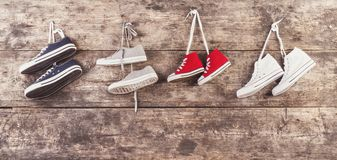 Sports shoes on the floor. Four pairs of sports shoes hang on a nail on a wooden fence background Royalty Free Stock Images