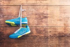 Sports shoes on the floor. Pair of sports shoes hang on a nail on a wooden fence background Royalty Free Stock Image