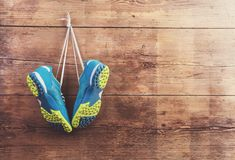 Sports shoes on the floor. Pair of sports shoes hang on a nail on a wooden fence background Stock Photography