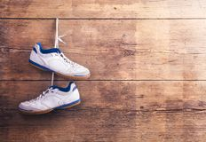 Sports shoes on the floor. Pair of sports shoes hang on a nail on a wooden fence background Royalty Free Stock Photo