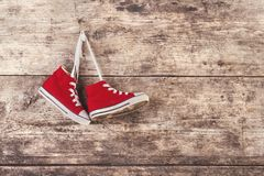 Sports shoes on the floor. Pair of red sports shoes hang on a nail on a wooden fence background Royalty Free Stock Photography