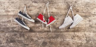 Sports shoes on the floor. Three pairs of sports shoes hang on a nail on a wooden fence background Royalty Free Stock Photo