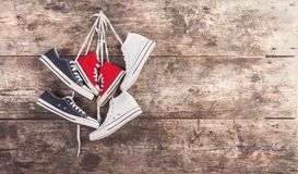 Sports shoes on the floor. Three pairs of sports shoes hang on a nail on a wooden fence background Royalty Free Stock Photos