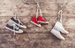Sports shoes on the floor. Three pairs of sports shoes hang on a nail on a wooden fence background Stock Images