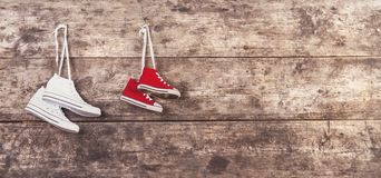 Sports shoes on the floor. Two pairs of sports shoes hang on a nail on a wooden fence background Royalty Free Stock Image