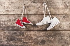 Sports shoes on the floor. Two pairs of sports shoes hang on a nail on a wooden fence background Stock Photo