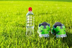 Sports shoes sneakers and bottle of water on a fresh green grass royalty free stock image