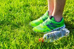 Sports shoes sneakers and bottle of water on a fresh green grass. royalty free stock photography