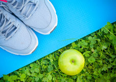 Sports shoes sneakers on  yoga mat and apple on fresh green grass Stock Photo