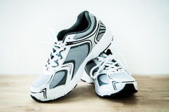 Sports shoes on a wooden floor Stock Photos