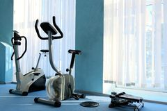 Sports simulators stand near the window with blinds. Exercise bikes for physical activity. Rest in the gym. Weekend with body royalty free stock photo