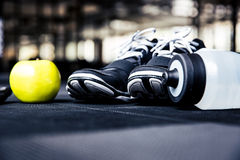 Sports sneakers, bottle with water and green apple Stock Photography