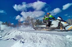 Sports snowmobile is riding at high speed. Extreme competitions on a sunny winter day. Concept quick movement. Side view. royalty free stock photos