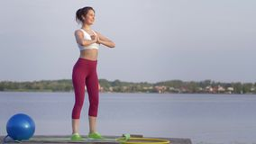 Sports squat, young woman with beautiful body performing fitness exercise during sports training in nature on bridge. Sports squat, young woman with beautiful stock video footage