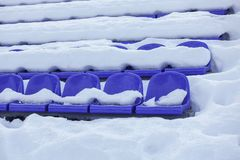 Sports stadium bleachers in winter, chairs of the fans - empty seats of grandstands covered by snow.  stock image