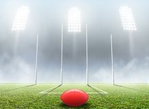 Sports Stadium And Goal Posts. An aussie rules football stadium with a ball and goal posts in the nighttime under illuminated floodlights - 3D render Stock Image