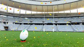 Sports stadium with red and yellow confetti falling. Animation of a rugby ball at sports stadium with red and yellow confetti falling royalty free illustration