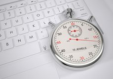 Sports stopwatch lying on a computer keyboard Royalty Free Stock Image