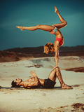 Sports stretching. Young sports couple doing acroyoga exercises on sand beach Royalty Free Stock Photo