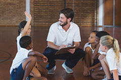 Sports teacher having discussion with his students Stock Image