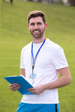 Sports Teacher. A male sports teacher stands outdoors on a field, he is holding a clipboard Royalty Free Stock Photography