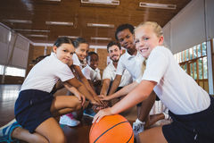 Sports teacher and school kids forming hand stack in basketball court Royalty Free Stock Images