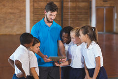 Sports teacher and school kids using digital tablet in basketball court Royalty Free Stock Image