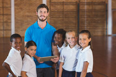 Sports teacher and school kids using digital tablet in basketball court Royalty Free Stock Images