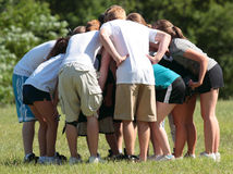 Sports Team Huddle. Group of teens in a strategy huddle during flag football game Royalty Free Stock Image
