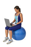 Sports and technology. Woman in fitness equipment sitting on a gym ball and working on a laptop.Conceptual image to show the universality and mobility of Stock Photography