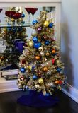 Sports themed Christmas tree in house by shelves of wine glasses. And knick knacks stock image