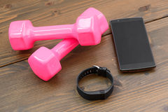 Sports tracker with smartphone. Wearable device, wirst watch type Sports tracker with smartphone and pink colored dumb-bell on a wooden board stock photos