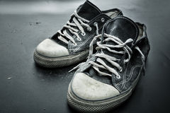 Sports trainers on the floor. Old sports trainers on the grey floor Royalty Free Stock Image