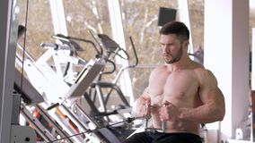 Sports training, attractive athlete guy bare-chested doing muscle building workout on traction simulator while working. Sports training, attractive athlete stock video