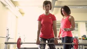 Sports training. The girl does exercises with a bar in the gym stock video