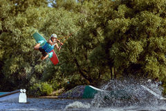 Sports training on a wakeboard. Jumping over water and tricks Stock Image