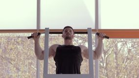 Sports training, young athlete with beautiful muscular body pulls up during power workout at fitness center. Sports training, young athlete man with beautiful stock footage