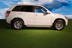 Sports utility vehicle. White SUV on green field against deep blue sky Stock Photography