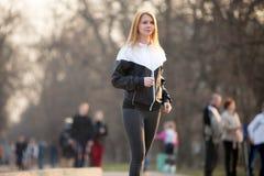 Sports walking in park. Sporty girl in sportswear walking practice in crowd in park Stock Image