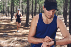 Sports watch couple. Trail running couple check time on their gps watch for tracking pace Royalty Free Stock Image
