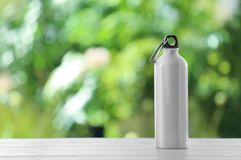 Sports water bottle on table against blurred background. Space for text stock photos