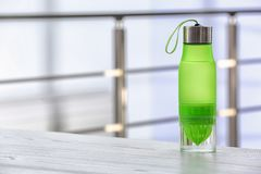 Sports water bottle on table against blurred background. Space for text stock images