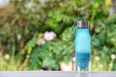 Sports water bottle on table. Against blurred background. Space for text stock image