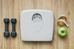 Sports and weight loss. Weight scale, healthy snack, measuring tape and dumbbells on a table, weight loss and sports concept, flat lay Stock Photography