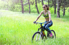 Sports woman with a bicycle in the forest. Summer bike ride, fre Stock Photos
